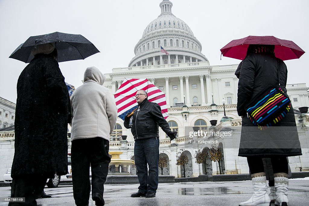 Boris Volk (2nd R) leads a tour group from Brooklyn, New York, at the U.S. Capitol on December 10, 2013 in Washington, DC. A winter storm that closed many federal government operations is expected to leave 3-5 inches of snow across the region.