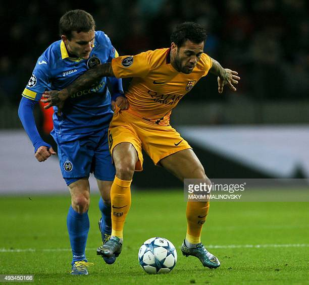 Borisov's Belarusian forward Mikhail Gordeychuk vies for the ball with Barcelona's Brazilian defender Dani Alves during the UEFA Champions League...
