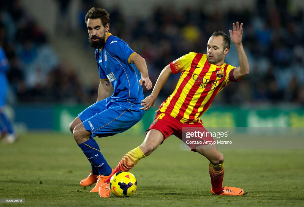 Borja Fernandez Fernandez (L) of Getafe CF competes for the ball with <a gi-track='captionPersonalityLinkClicked' href=/galleries/search?phrase=Andres+Iniesta&family=editorial&specificpeople=465707 ng-click='$event.stopPropagation()'>Andres Iniesta</a> (R) of FC Barcelona during the La Liga match between Getafe CF and FC Barcelona at Coliseum Alfonso Perez on December 22, 2013 in Getafe, Spain.