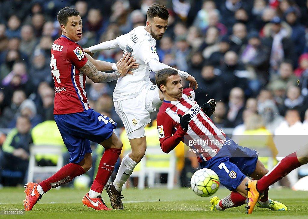 Borja Mayoral of Real Madrid shoots on goal past Jose Maria Gimenez (L) and Antoine Griezmann of Club Atletico de Madrid during the La Liga match between Real Madrid CF and Club Atletico de Madrid at Estadio Santiago Bernabeu on February 27, 2016 in Madrid, Spain.