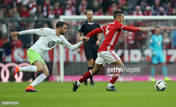 Borja Mayoral of Wolfsburg holds Thiago Alcantara of Muenchen during the Bundesliga match between Bayern Muenchen and VfL Wolfsburg at Allianz Arena...