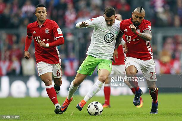 Borja Mayoral of Wolfsburg is challenged by Arturo Vidal of Muenchen during the Bundesliga match between Bayern Muenchen and VfL Wolfsburg at Allianz...