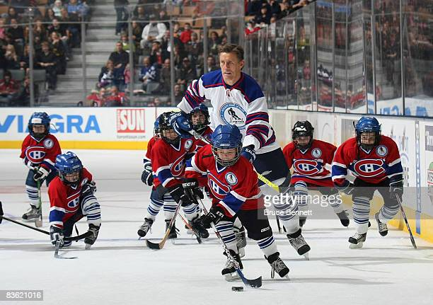 Borje Salming of the All Star Legends is surrounded by youth players sporting Montreal Canadien jerseys at the Legends Classic Game on November 9...