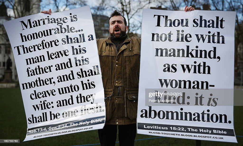Born again Christian Carl Hamblin holds banners quoting the Bible as he stands in Parliament Square on February 5, 2013 in London, England. Later Parliament will hold a vote on whether to allow homosexual couples to marry.