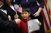 Born in China Zachary Shields holds up his citizenship certificate during the children's citizenship ceremony at the US Citizenship and Immigration...