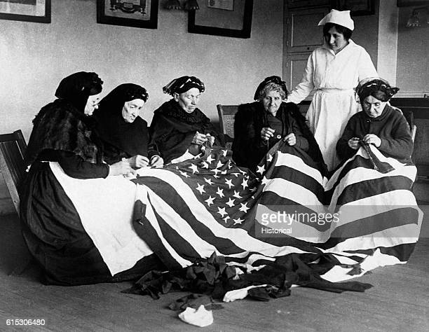 Born in Hungary Galicia Russia Germany and Rumania these patriotic elderly women make flags as their flagmaking instructor Rose Radin stands behind...