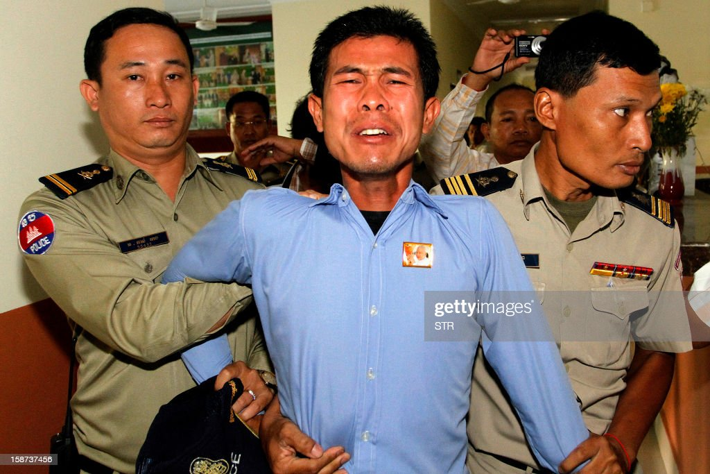 Born Samnang (C), one of two men convicted for the 2004 murder of a prominent labour leader, is led by police as they make an appearance at the Court of Appeals in Phnom Penh on December 27, 2012. Cambodian rights campaigners on December 27 condemned the sentencing of the two men to 20 years in prison for the 2004 murder of a prominent labour leader, saying the verdict was deeply flawed.