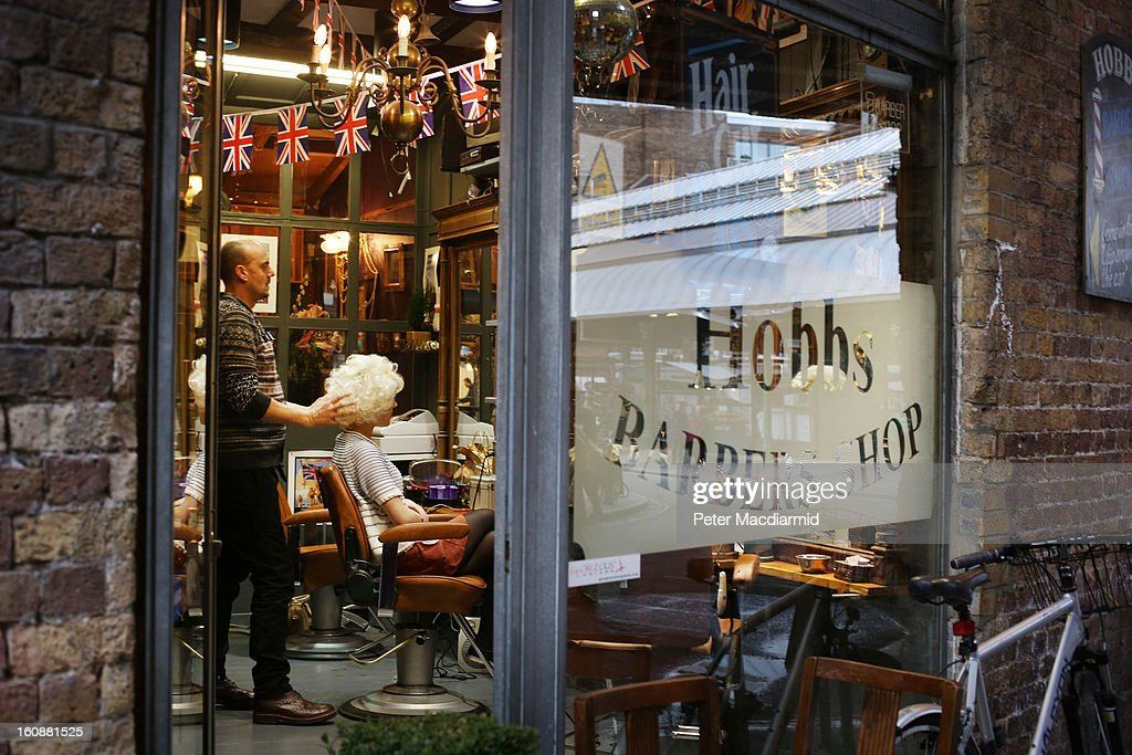 Borough Market (R) is reflected in the window of Hobb's barber shop under the railway arches on February 7, 2013 in London, England. Borough Market, London's oldest since 1756, has recently completed renovation and today had it's first day of full trading.