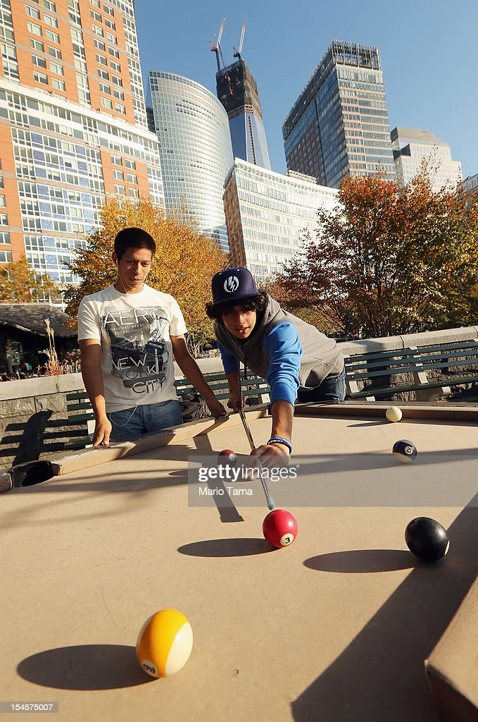 Borough of Manhattan Community College (BMCC) students play pool in Lower Manhattan as One World Trade Center (TOP C) rises under construction on October 22, 2012 in New York City. The Census Bureau reported last month that between 2000 and 2010 the downtown population grew by nearly 40,000 people, in spite of the September 11 terrorist attacks at the World Trade Center. One World Trade Center is scheduled to open in 2014 at the symbolic height of 1,776 feet and will be the tallest building in the Western Hemisphere.