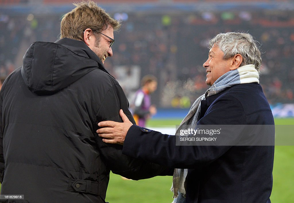 Borussia Dortmund coach Jurgen Klopp (L) and FC Shakhtar coach Mircea Lucescu greet one another prior to the UEFA Champions League round 16 football match in Donetsk on February 13, 2013.