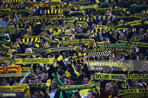 Borussia Dortmund fans hold their scarves during the UEFA Champions League Group F match between Borussia Dortmund and Olympique de Marseille at...