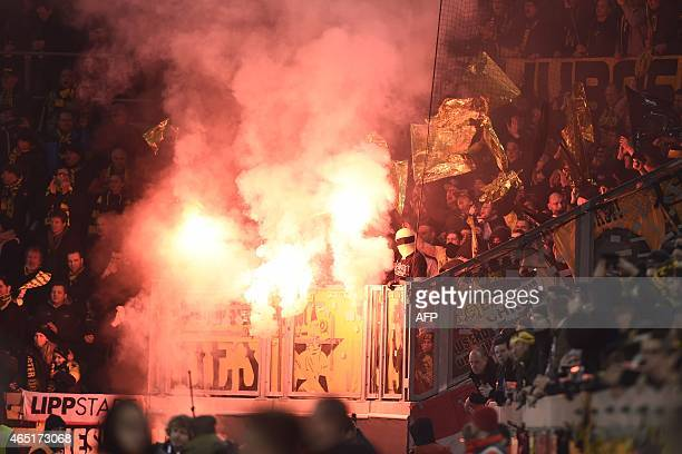 Borussia Dortmund's fans burn flares at the start of the German football Cup DFB Pokal round of 16 game between German third division Dynamo Dresden...