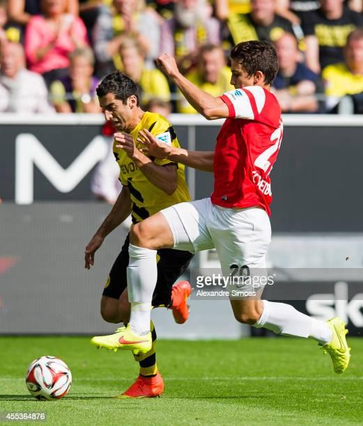 Borussia Dortmund's Henrikh Mkhitaryan in action against Freiburg's MarcOliver Kempf during the Bundesliga match between SC Freiburg and Borussia...