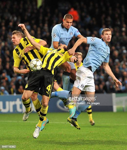 Borussia Dortmund's Jakub Blaszczykowski and Neven Subotic go up for a header against Manchester City's Jack Rodwell and Edin Dzeko