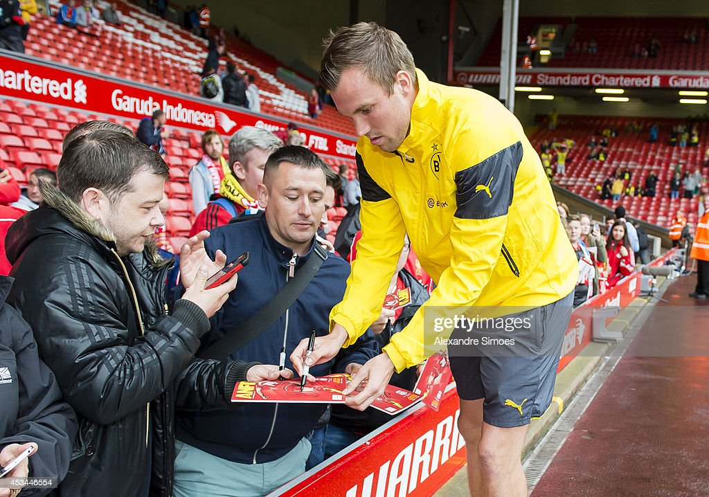 Borussia Dortmund's Kevin Grosskreutz is giving autographs before the pre season friendly match between Liverpool FC and Borussia Dortmund at Anfield on August 10, 2014 in Liverpool, England.
