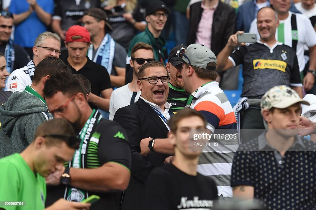 Borussia Monchengladbach's director of sport Max Eberl (C) shake hands with fans ahead of the UEFA Champions League group C football match between Manchester City and Borussia Monchengladbach at the Etihad stadium in Manchester, northwest England, on September 14, 2016. / AFP / PAUL