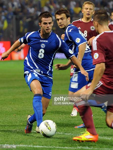 Bosnia and Hercegovina's Miralem Pjanic vies for the ball with Latvia's defence during the FIFA 2014 World Cup qualifying football match between...