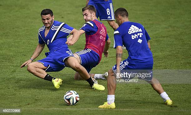 Bosnia and Herzegovina's defender Sead Kolasinac challenges midfielder Tino Sven Susic during a training session at the Antonio Fernandez Stadium in...