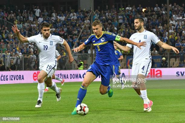 Bosnia Herzegovina's forward Edin Dzeko vies with Greece's defenders Sokratis Papastathopoulos and Kostas Manolas during the FIFA World Cup 2018...