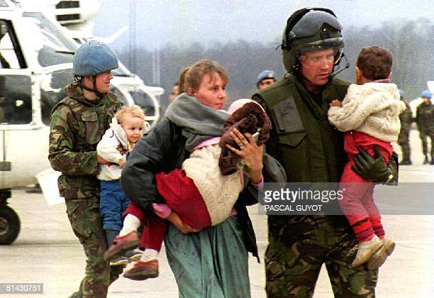 BosniaHercegovina UN soldiers carry children and escort a woman holding another child from Srebrenica upon their arrival by helicopter at a Tuzla...
