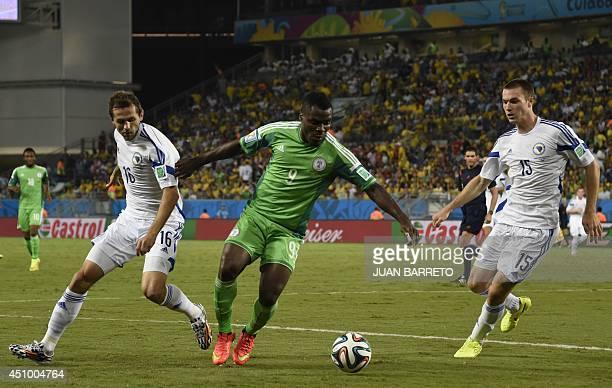 BosniaHercegovina's midfielder Senad Lulic and BosniaHercegovina's defender Toni Sunjic fight for the ball with Nigeria's forward Emmanuel Emenike...