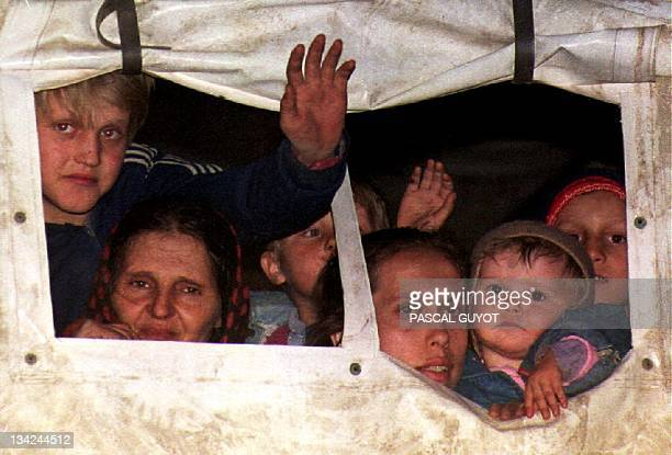 A group of Bosnian refugees peer out of a UN truck after arriving in Tuzla late 20 Mar They are part of some 100 wounded and 500 women and children...