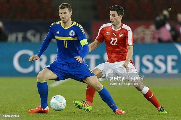 BosniaHerzegovina's foward Edin Dzeko vies with Switzerland's defender Fabian Schaerduring the friendly football match between Switzerland and...