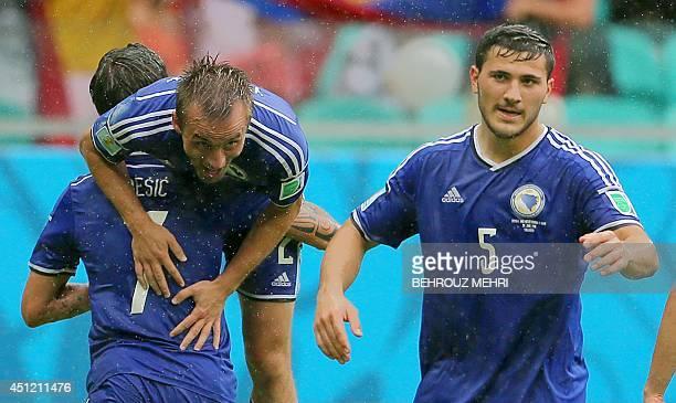 BosniaHerzegovina's midfielder Avdija Vrsajevic is lifted by BosniaHerzegovina's midfielder Muhamed Besic as BosniaHerzegovina's defender Sead...