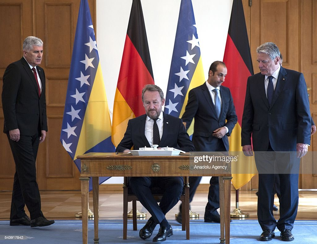 Bosniak Member of the Presidency of Bosnia and Herzegovina Bakir Izetbegovic (C) signs guestbook as he meets with President of Germany Joachim Gauck (R) during tripartite Presidency of Bosnia and Herzegovina's official visit at the Schloss Bellevue in Berlin, Germany on June 30, 2016.