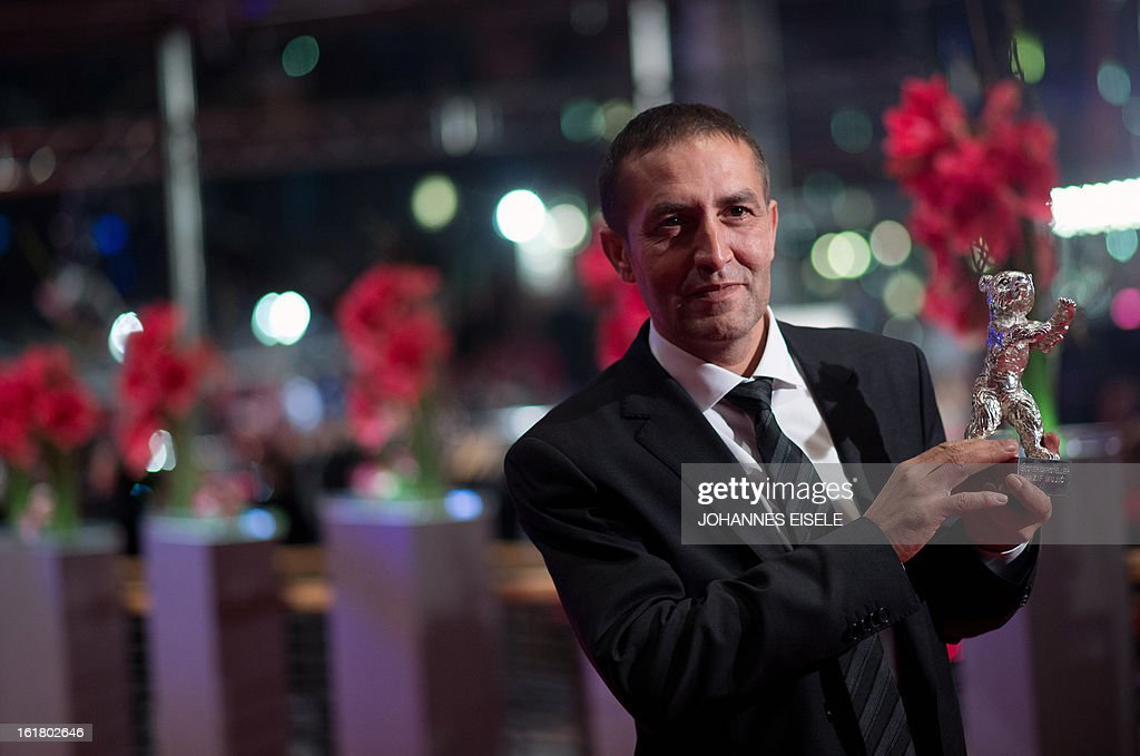 Bosnian actor Nazif Mujic holds the Silver Bear for Best Actor he received for the film 'Epizoda u zivotu beraca zeljeza' (An episode in the life of an iron picker) as he poses after the awards ceremony of the 63rd Berlinale Film Festival, in Berlin on February 16, 2013. AFP PHOTO / JOHANNES EISELE