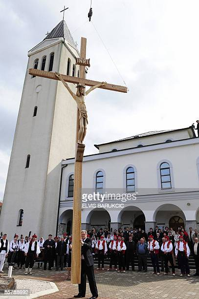 Bosnian artist Branko Ivankovic guides a crucifix towards the site where it will stand outside a church in the WesternBosnian town of Livno on April...