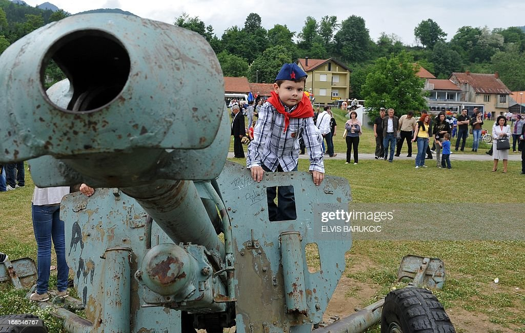 A Bosnian boy, dressed as socialist youth (Tito's pioneers), is seen next to a World War II cannon in the Southern-Bosnian town of Jablanica, on May 11, 2013. A crowd of several thousand socialist supporters and sympathisers gathered in Jablanica to commemorate the 70th anniversary of The Battle on the river Neretva, one of the most famous battles of World War II in Yugoslavia. The battle was fought by Tito's Partisans who were vastly outnumbered and outgunned by German forces and their domestic helpers. The Partisans carried a large number of wounded fighters and were followed by several thousands of civillians who were fleeing in front of a German offensive.