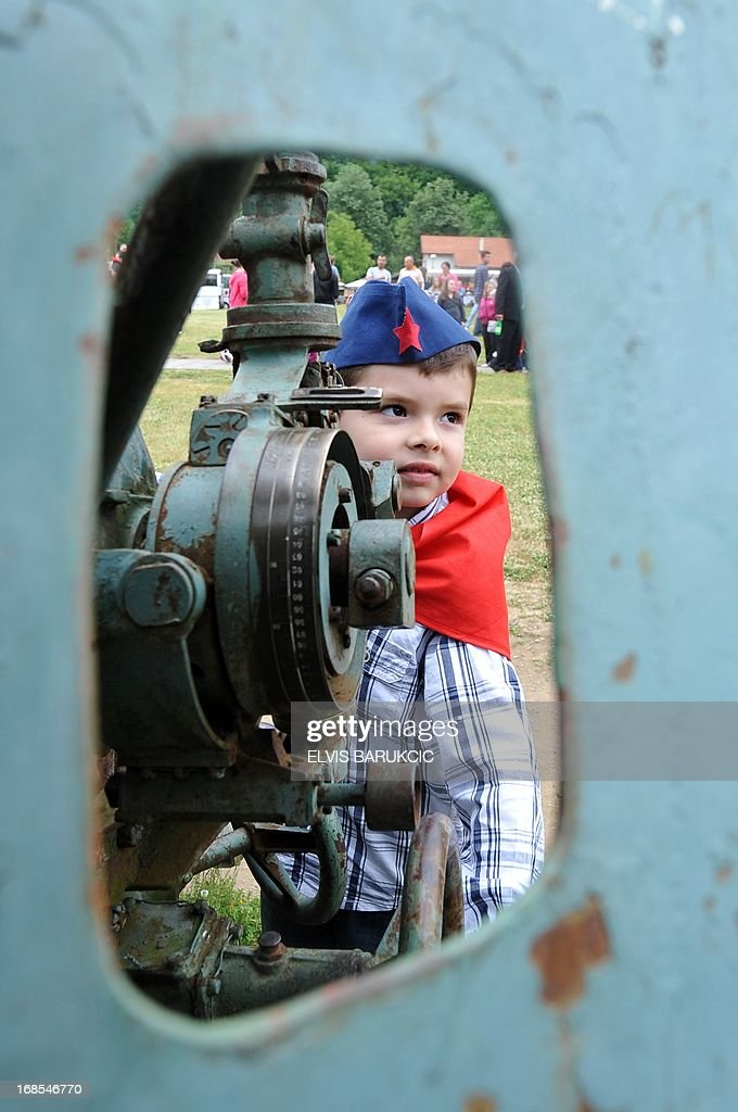 A Bosnian boy, dressed as socialist youth (Tito's pioneers), is seen next to a World War II cannon in the Southern-Bosnian town of Jablanica, on May 11, 2013. A crowd of several thousand socialist supporters and sympathisers gathered in Jablanica to commemorate the 70th anniversary of The Battle on the river Neretva, one of the most famous battles of World War II in Yugoslavia. The battle was fought by Tito's Partisans who were vastly outnumbered and outgunned by German forces and their domestic helpers. The Partisans carried a large number of wounded fighters and were followed by several thousands of civillians who were fleeing in front of a German offensive. AFP PHOTO / ELVIS BARUKCIC