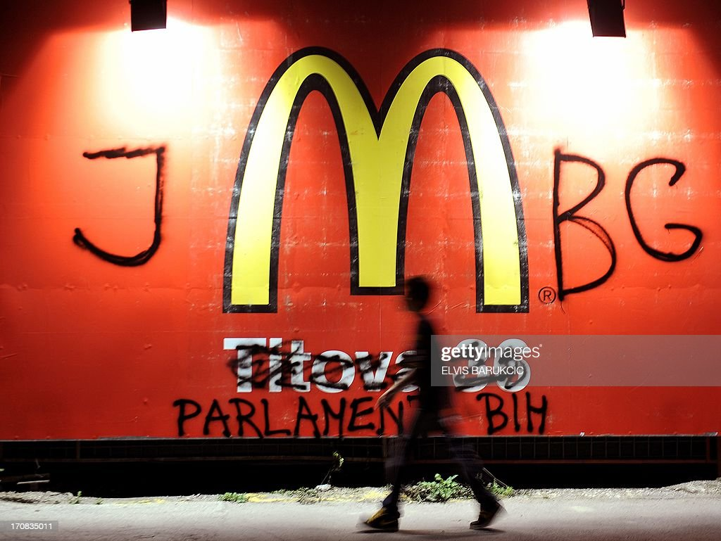 Bosnian boy passes by a billboard advertising McDonalds reastaurants while some of 3,000 Bosnians gather, late on June 18, 2013 in front of the parliament in Sarajevo. Bosnians gathered, late on June 18 for a thirteenth day of protests against a legal void which has left all babies born since February without identity numbers, meaning they cannot be issued passports or access medical care. The newborns have fallen victim to an ongoing dispute between Muslim, Croat and Serb deputies of Bosnia's central parliament who for more than two years have been bickering over a draft law on the personal identification numbers that are necessary for all documents and services. JMBG is the personal identification number. (The sign 'Crime Scene' is being projected onto the Parliament building).