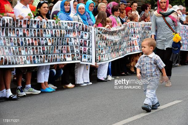 A Bosnian boy walks by women holding a banner with picture of people killed in Srebenicq as they await the arrival of the trucks transporting body...