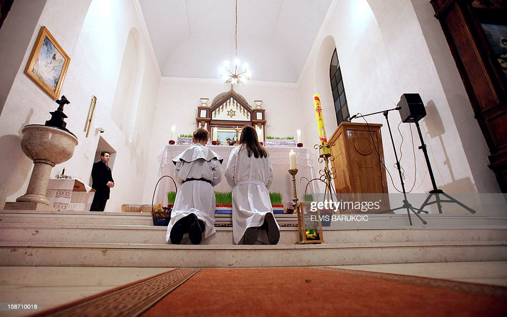 Bosnian Croat children prepare for the Midnight Christmas Mass at a church in the village of Morancani, near the Northern-Bosnian town of Tuzla, late on December 24, 2012.