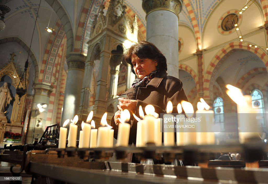 A Bosnian Croat woman lights candles after a Christmas Mass at Sarajevo's Cathedral of The Heart Of Jesus, early on December 25, 2012. AFP PHOTO / ELVIS BARUKCIC