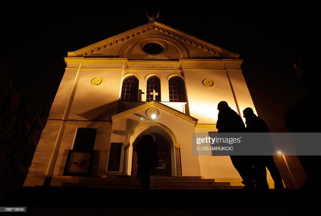 Bosnian Croats stand outside the church before attending the Midnight Christmas Mass in the village of Morancani, near the Northern-Bosnian town of Tuzla, late on December 24, 2012.