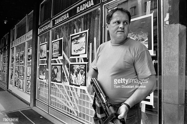 Bosnian fighter armed with an AK47 stands in front of images of massacres alledgedly by Serbian forces During the 47 months between the spring of...