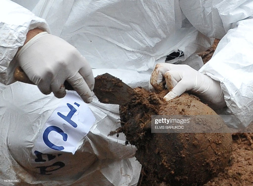 Bosnian forensic expert cleans a human skull found among body remains, while excavating a potential mass grave site in the village of Misevici, a western suburb of Sarajevo, on December 5, 2012. The forensic team reacted upon an instruction by the Sarajevo District Prosecutor. Only two complete body remains were retrieved on Wednesday, more are expected to be found as the excavation continues. Bodies are believed to belong to Bosnian Muslims killed in the spring of 1992, by Bosnian Serb forces.