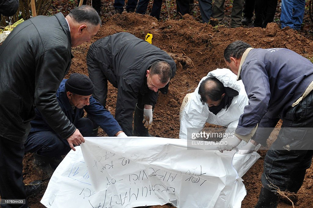 Bosnian forensic experts gather human body remains, found while excavating a potential mass grave site in the village of Misevici, a western suburb of Sarajevo, on December 5, 2012. The forensic team reacted upon an instruction by the Sarajevo District Prosecutor. Only two complete body remains were retrieved on Wednesday, more are expected to be found as the excavation continues. Bodies are believed to belong to Bosnian Muslims killed in the spring of 1992, by Bosnian Serb forces.