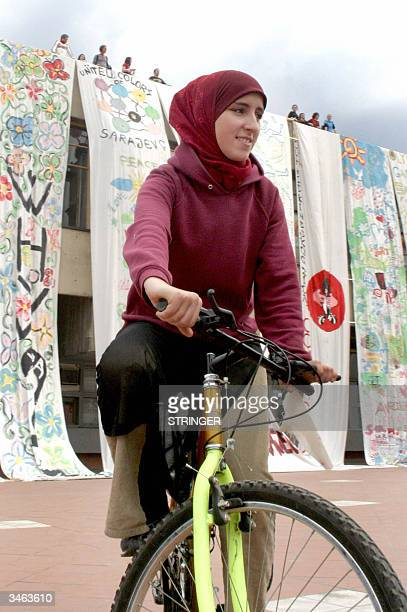 Bosnian girl rides a bicycle as youth group behind unrolls painted canvas during performance called 'Ask Sarajevo' in front of Sarajevo Youth Center...