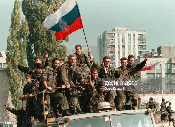 Bosnian government soldiers atop a truck wave a captured Serb flag in Zenica Wednesday Oct 11 1995 The troops were coming back to their base in...