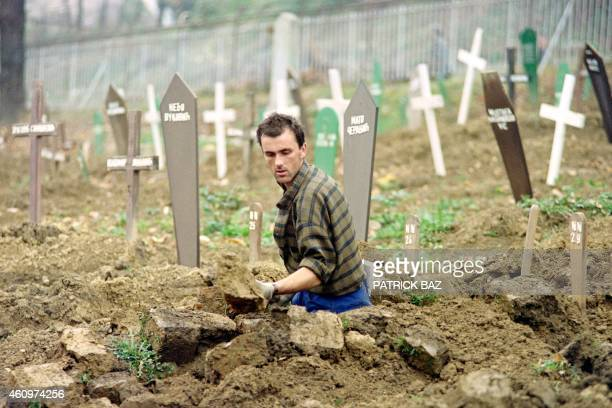 A Bosnian grave digger excavates in a football stadium in Sarajevo widening the main cemetery on November 05 1992 Christians and Muslims are burried...