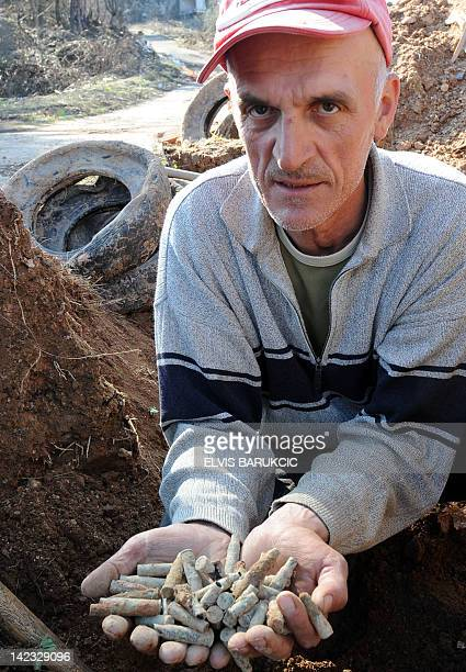 Bosnian man Daut Nezovic shows brass bullets he found by digging on the slpoes of mount Trebevic north of Bosnian capital Sarajevo on April 2 2012...