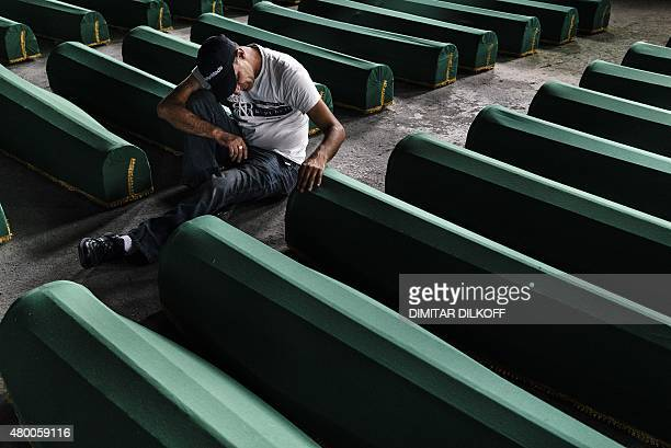 A Bosnian man mourns by a coffin his relative in Srebrenica on July 9 2015 where 136 bodies found in mass grave sites in eastern Bosnia will be...
