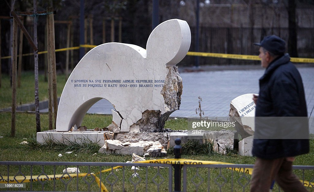 A Bosnian man walks past a damaged monument late on January 14, 2013 in Mostar. A monument to Bosnian Muslim soldiers killed in the country's 1992-1995 war was damaged in a blast early on January 14 in Mostar, a town divided between its Croat and Muslim communities, police said. Police official Srecko Bosnjak said no one was injured in the blast, which took place outside the city hall in downtown Mostar.