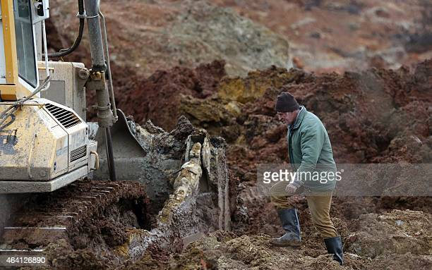 A Bosnian man walks towards an excavator as rescue workers look for bodies following a land slide at a coal mine located close to the Bosnian village...
