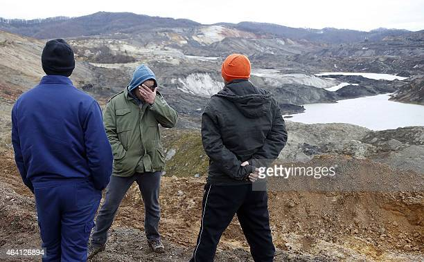 Bosnian men gather as they watch the rescue work following a land slide at a coal mine located close to the Bosnian village of Dubrave near the...