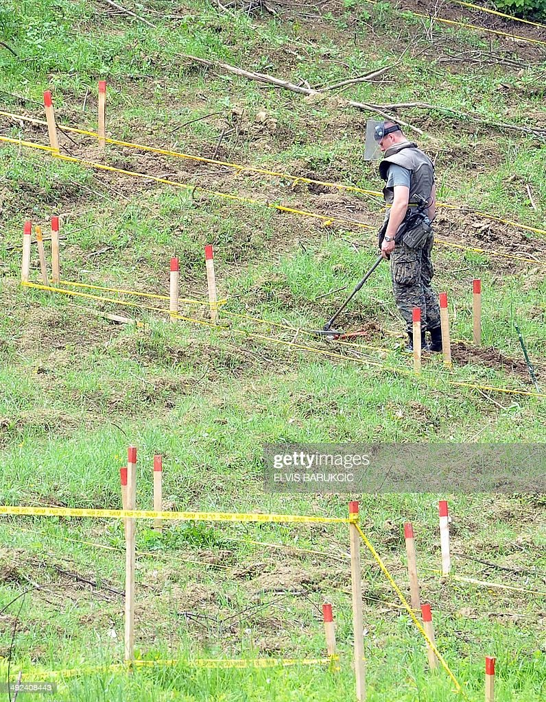 Bosnian mine clearance experts search a field after flood waters receded from the village of Cekrekcije near Sarajevo on May 20 2014 The river Bosna...